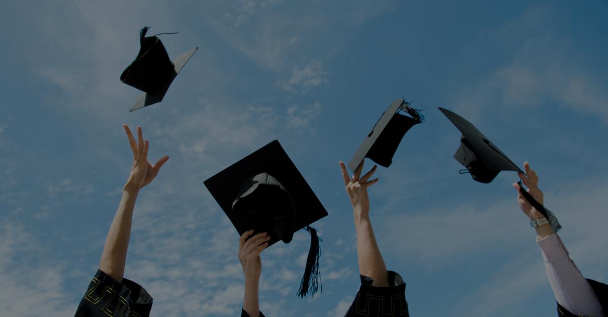 Studenten werfen ihren Hut in die Luft nach Abschluss
